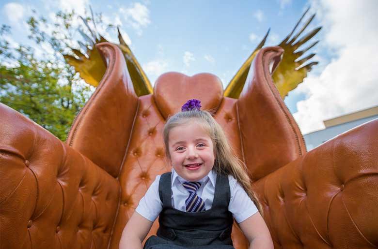 School girl sat on one of the three Kirkby thrones