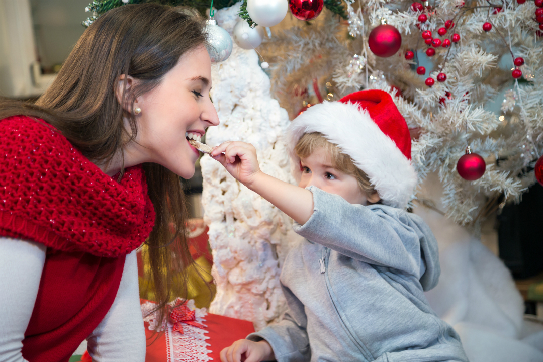 Woman and child eat cookies by Christmas tree