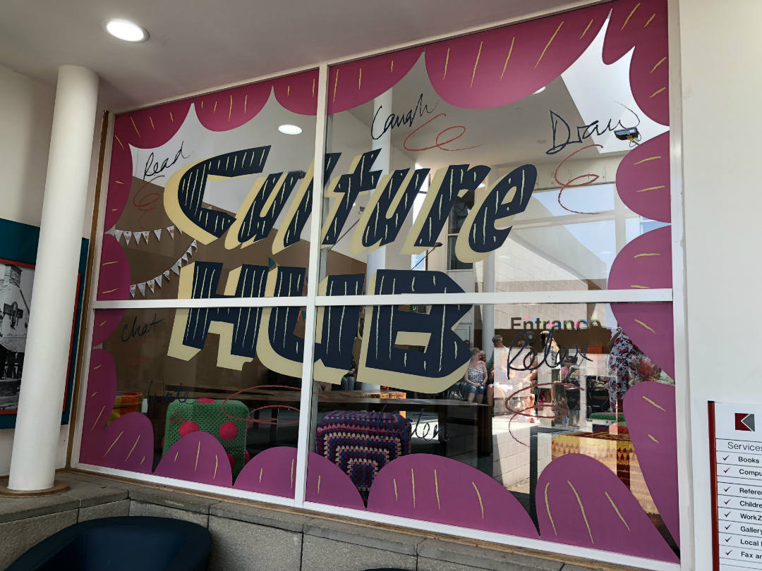 Window at Huyton Library with Culture Hub logo