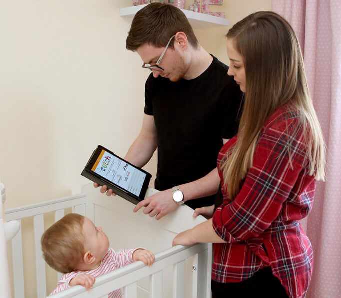 Mother and father with a tablet and a baby