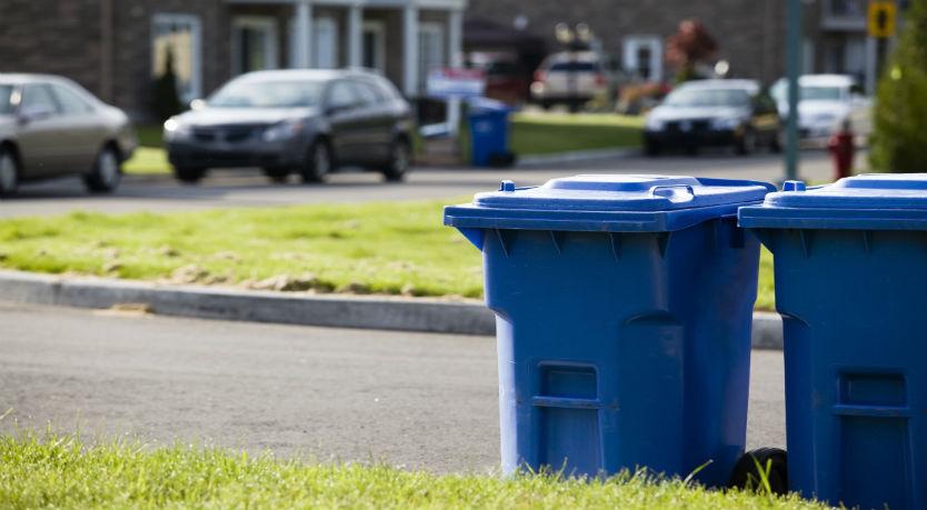 Blue wheelie bin by the side of a road