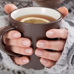Gloved hands trying to keep warm by holding a hot drink