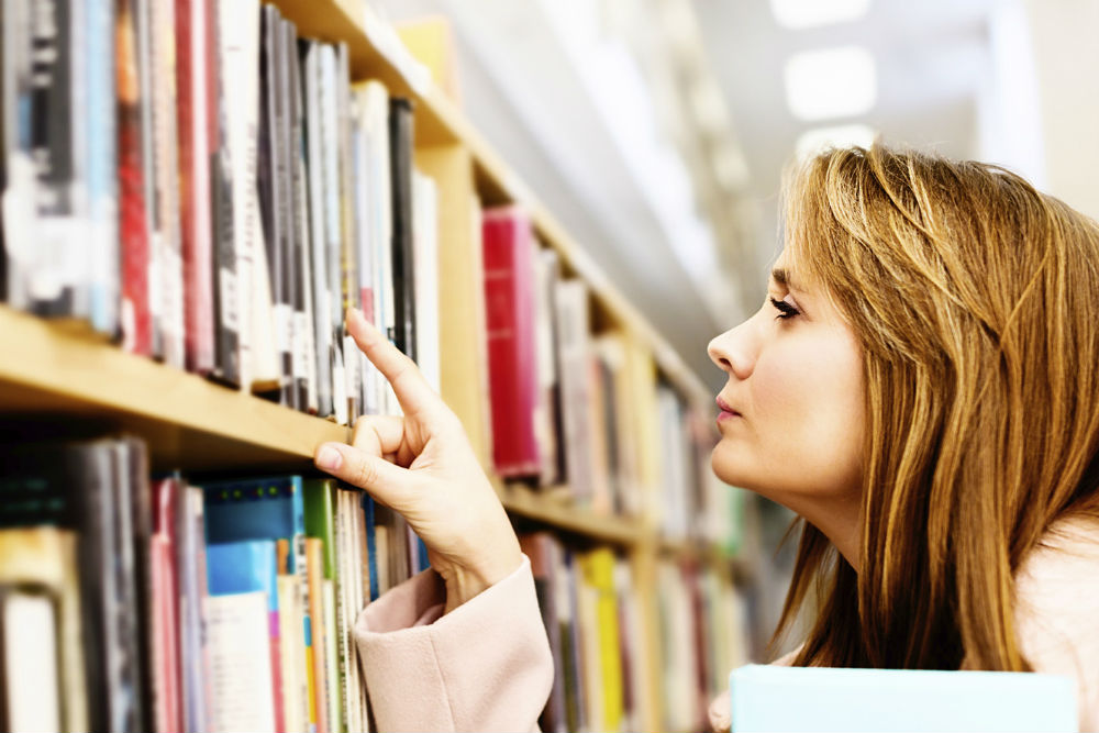 Woman browses books in library
