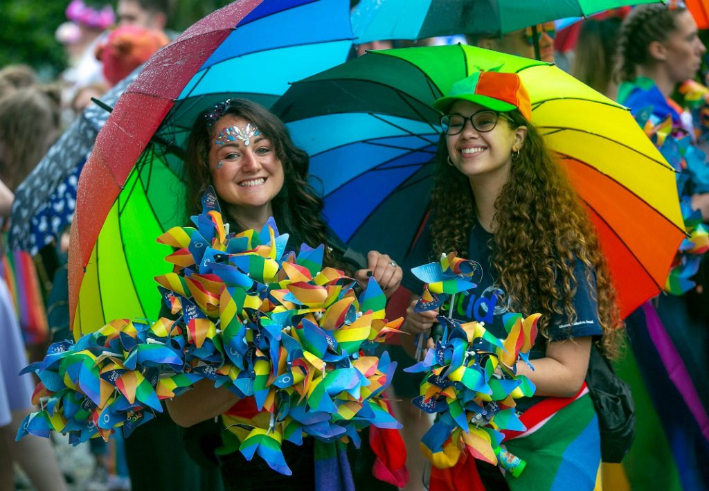 Revellers at Pride in Liverpool shelter under a rainbow umbrella