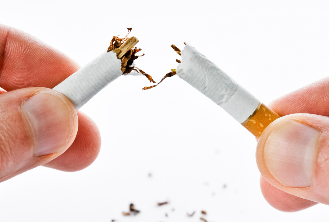 Cigarette being snapped in half as smoker quits smoking