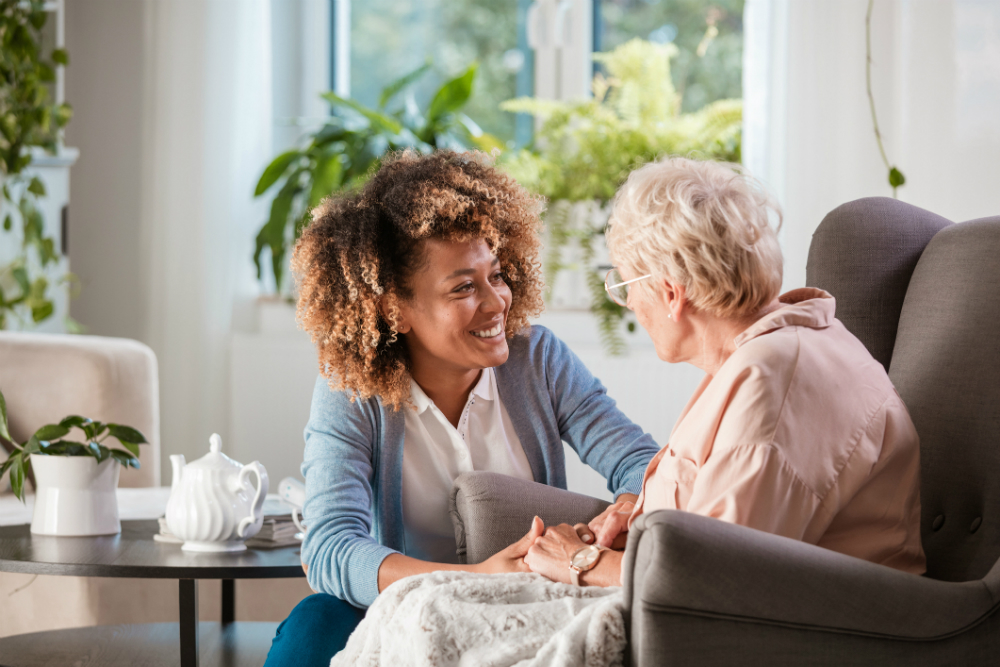 Friendly nurse supports elderly lady at home