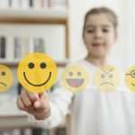 Little girl with smiley emoji touchscreen