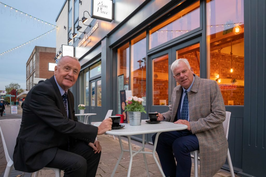 Cllr Graham Morgan and Cllr Tony Brennan enjoy a coffee outside Eton Place, one of the businesses to benefit from a new shop front as part of the council's Huyton Village improvement works.