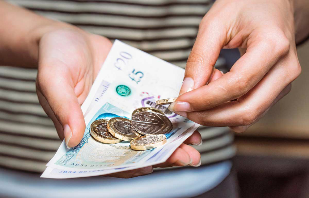 hands holding coins and notes