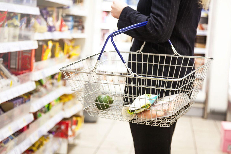shopper carrying basket in supermarket
