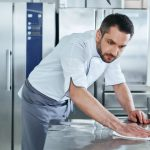 Chef in a restaurant kitchen cleaning as part of food safety and hygiene regulations