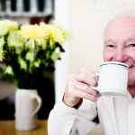This happy looking old man in his 80s drinks coffee, relaxed and smiling.