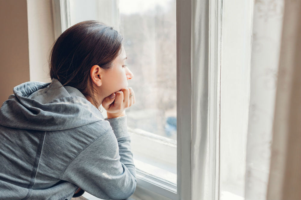 Woman looking out of window while self-isolating