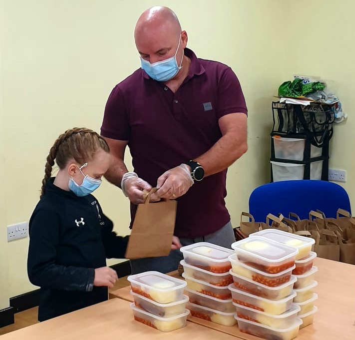 Cllr John Donnelly and his daughter Maizy help out with packaging up hot meals for delivery to elderly or vulnerable people