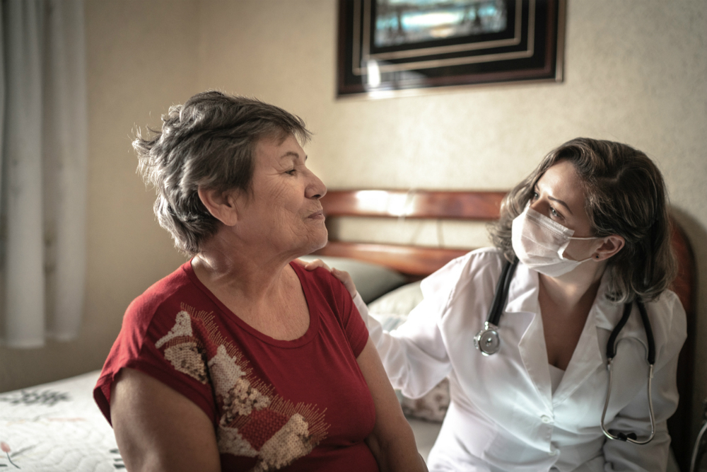 Carer wearing mask with older lady