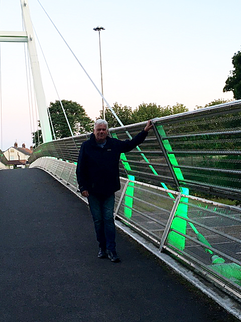 Cllr Morgan on the Greystone Bridge which is lit up in green