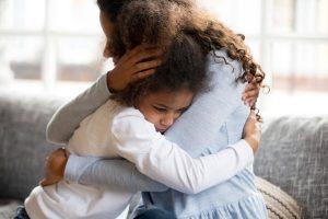 women sits on sofa hugging young girl