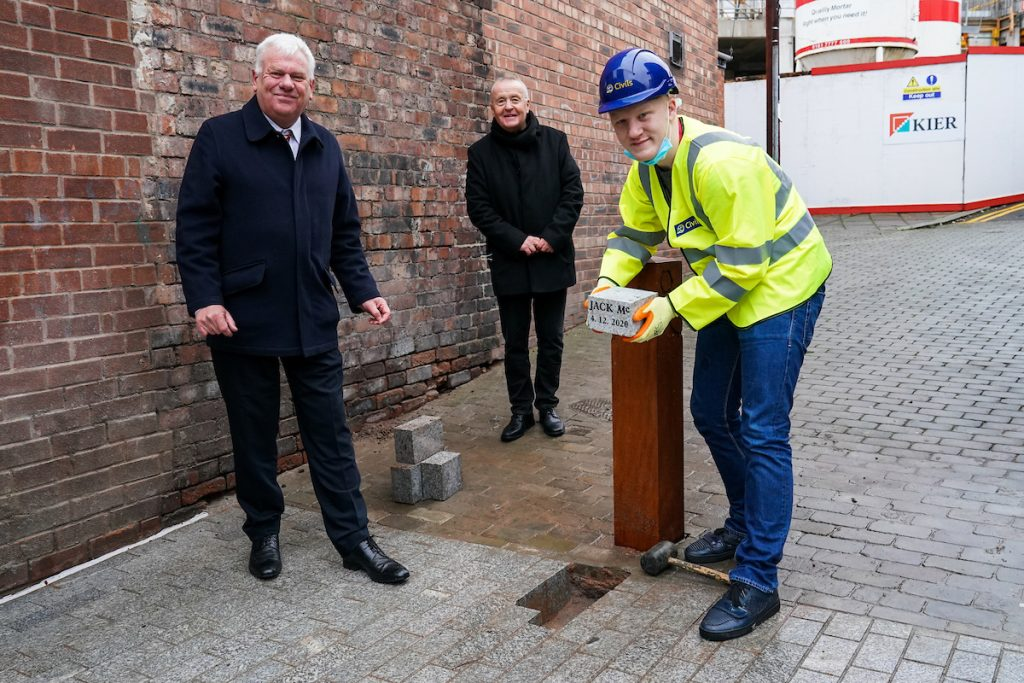 Cllr Graham Morgan, Cllr Tony Brennan and local resident Jack, laying the final piece of paving on Eccleston Street, Prescot.