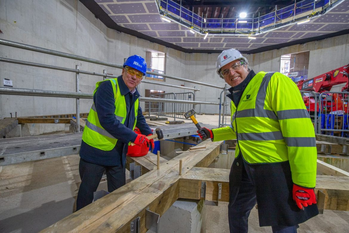 Cllr Graham Morgan and Metro Mayor Steve Rotheram getting 'hands on' with the installation of the timber frame theatre at The Shakespeare North Playhouse